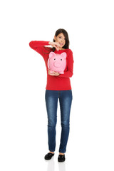 Happy woman putting a coin to piggybank.