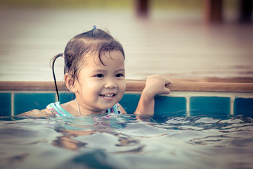 Cute little girl in swimming pool in vintage color style