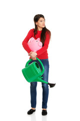 Woman with a watering can and piggybank.