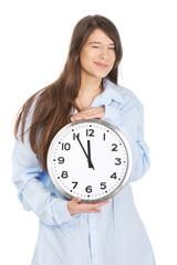 Morning woman in big shirt holding clock.