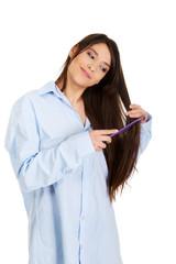 Morning woman in big shirt combing hair.