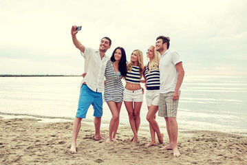 happy friends on beach and taking selfie