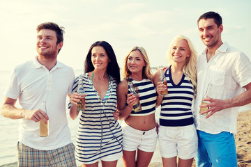 smiling friends with drinks in bottles on beach