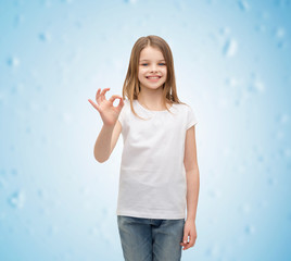 little girl in white t-shirt showing ok gesture