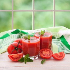 Tomato juice with vegetables on white wooden table.