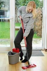 Hausfrau bei Frühjahrsputz wischt Parkett Boden