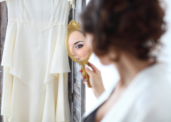 Gentle young bride looks in the mirror