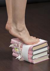 Caucasian female feet standing tiptoe on stack of books closeup