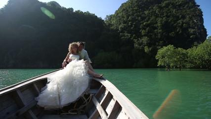 european wedding couple sitting in longtail boat