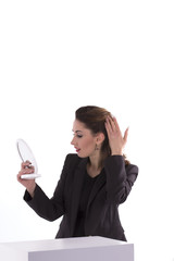woman looking in a  mirror at the workplace