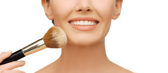 woman applying powder foundation with brush