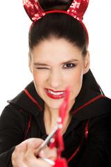 Woman in devil costume blinks eye.
