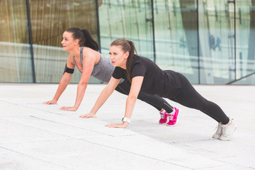 Two women doing push-ups exercises