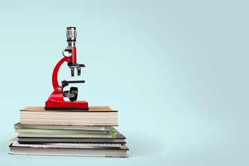 School. Color photo of a microscope on stack of books