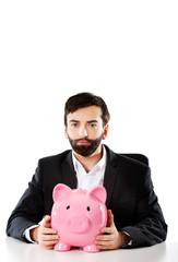Businessman with piggybank by a desk.