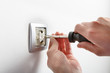 Electrician installing a light switch - 81938087