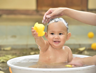 Baby bathing in the white tub, baby playing yellow duck