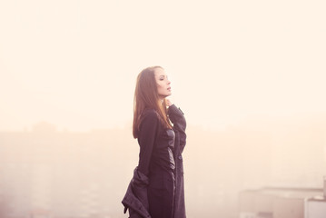 beautiful young girl in black enjoys the freedom in a morning