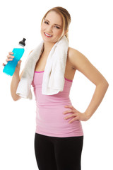 Woman in fitness clothes drinking isotonic drink.