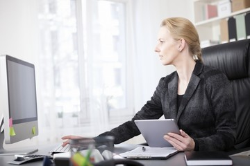 Businesswoman with Tablet Using a Desktop Computer