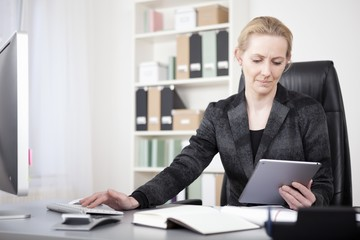 Manageress with Tablet Typing on Desktop Computer