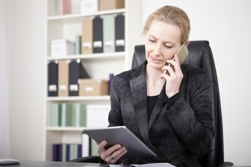 Manageress Holding a Tablet While Calling on Phone