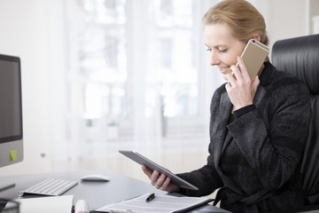 Happy Businesswoman with Tablet Talking on Phone