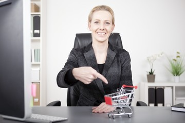 Businesswoman Pointing at Small Cart on her Desk