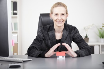 Businesswoman Covering Miniature House on Table