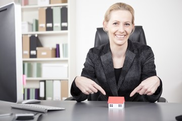 Businesswoman Pointing at Miniature House on Desk