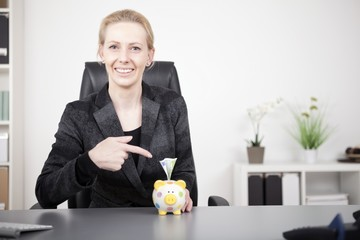 Businesswoman Pointing at Piggy Bank with Cash