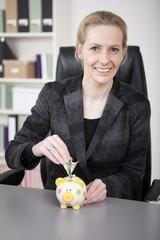 Smiling Businesswoman Saving Money to Piggy Bank