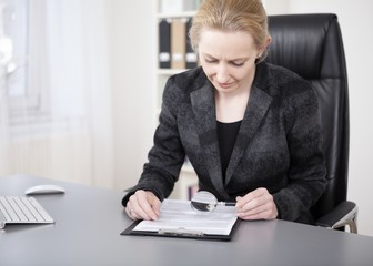 Serious Office Woman Reading with Magnifying Glass