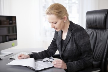 Manageress Scanning Papers with Magnifying Glass