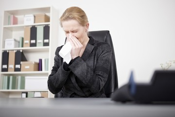 Manageress Sneezing with Eyes Closed at her Office