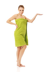 Woman wrapped in towel holding something on palm.