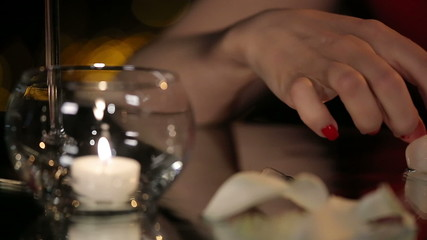 Female Hands Playing with a Candle and Melting Ice Cubes on the