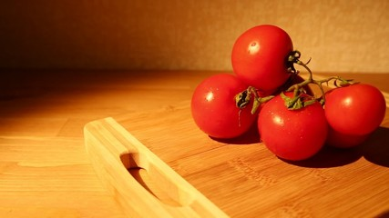 A bunch of tomatoes with water drops on a cutting board