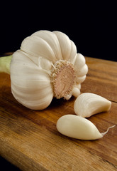 Two segments of garlic on a kitchen board.