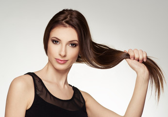 Young attractive brunette touching her healthy shiny hair.