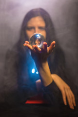 The woman holds a magic sphere