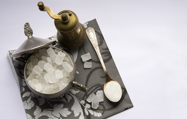 sugar crystals in silver spoon and grinder