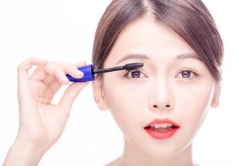 Asian female applying mascara