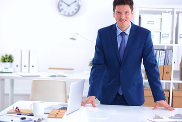 Confident successful young businessman leaning arms on his desk