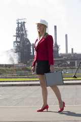 Businesswoman wearing a hard hat in an industrial environment