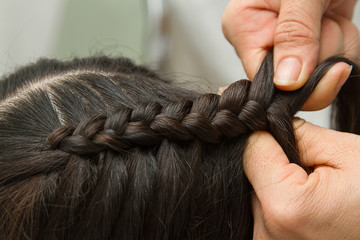 Hairdresser make braids in beauty salon