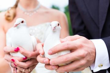 Brautpaar bei Hochzeit mit weißen Tauben