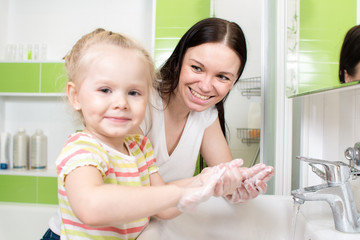 young woman and her daughter washing hands with soap in bathroom