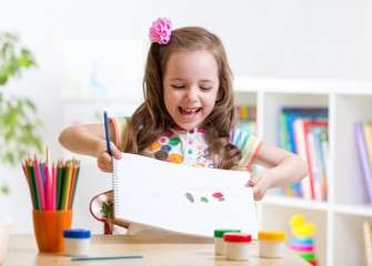 child girl painting and showing painting in nursery