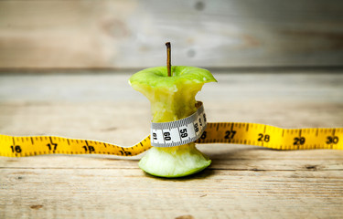 fruit. apple core with a tape measure around it.